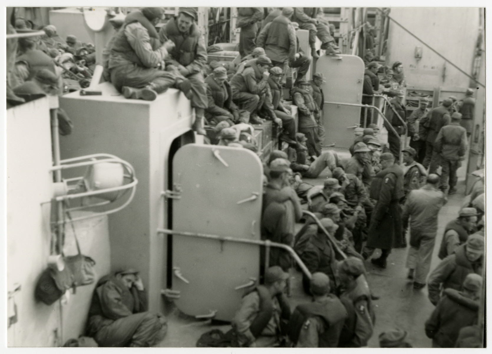 "American troops gather on deck on their return to the United States.  The donor, Henry Landman, is lying in the bottom left.  The original caption reads: ""Going home on board the converted Queen Elizabeth."""