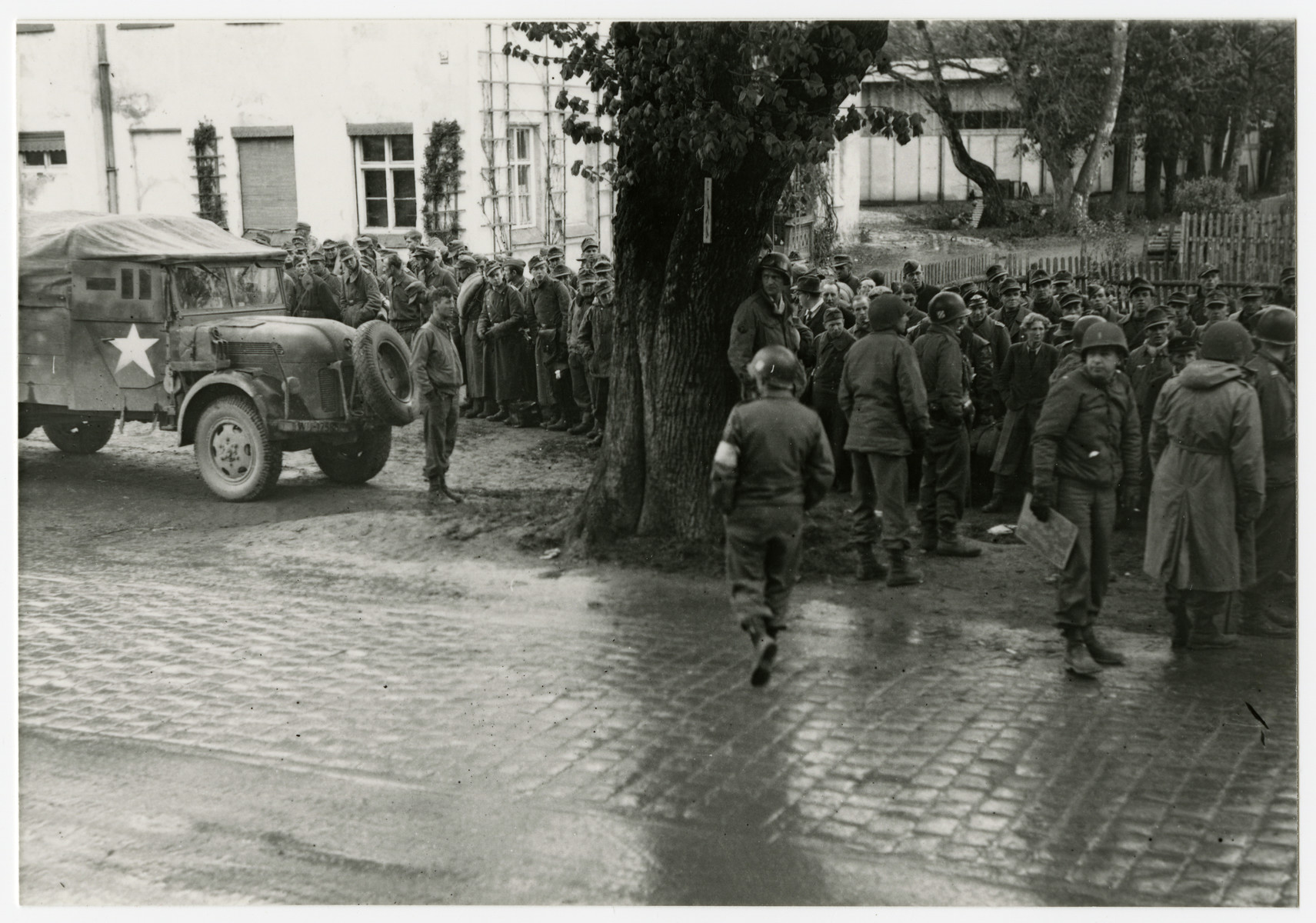 "American soldiers stand guard over recently captured German prisoners.  The original caption reads"" Munich 1945 -- We don't know what to do with all the prisoners."""