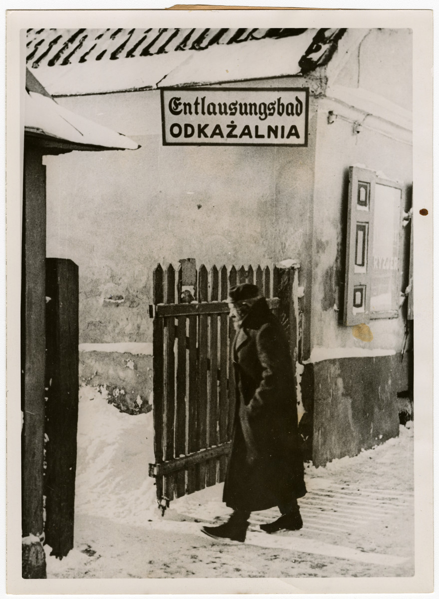 An elderly Polish Jews enters a delousing bath.    Original caption reads: Streifzug mit der deutschen Polizei durch ein ghetto im Osten Etwas was auch erzwungen werden musste, war der Gang der Juden ins Entlausungsbad, der monatlich einmal durchgeführt wird, auch wenn es den Kindern Israels keine grosse Freude bereitet.   [Raid with German police through a ghetto in the East: The Jews had to be coerced to the delousing bath, the process happens once a month. The children of Israel were not happy about the delousing.]