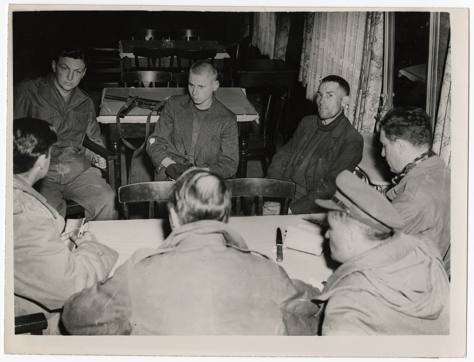 United States soldiers listen intently as political prisoners tell their story.   Original caption reads:  The Nazis Burn the Living When troops of the Ninth U.S. Army reached Gardelegen, Germany, they found the still- smoldering bodies of more than 1,000 political prisoners whom the Nazis had forced into a fuel soaked barn and burned to death. A mass of human flesh was smoking when American troops arrived on the scene and discovered from fugitives of the concentration camp that the atrocity had been committed by German troops and Luftwaffe personnel from a nearby airfield. Residents of the town of Gardelegen, 27 miles northwest of Madgeburg, were immediately compelled by U.S. officers to disinter approximately 700 partially buried dead and to bury all the charred victims.   THIS PHOTO SHOWS: A U. S. soldier (left) listens with clenched fists as two survivors of the barn funeral pyre tell their stories to war correspondents. Vladimire Wognia (center) of Lwow, Poland, imprisoned for releasing Polish prisoners being sent to Germany in 1942, ran through a hole in the burning barm, was shot at and ran back. Later, he escaped again and shouted in German to the Nazi guards to stop shooting. The brief confusion allowed him to escape in the dark. Eugene Sieradzki (right) kept alive by keeping his mouth to a hole in the barn. He was covered with bodies from Friday, April 13, until Sunday.