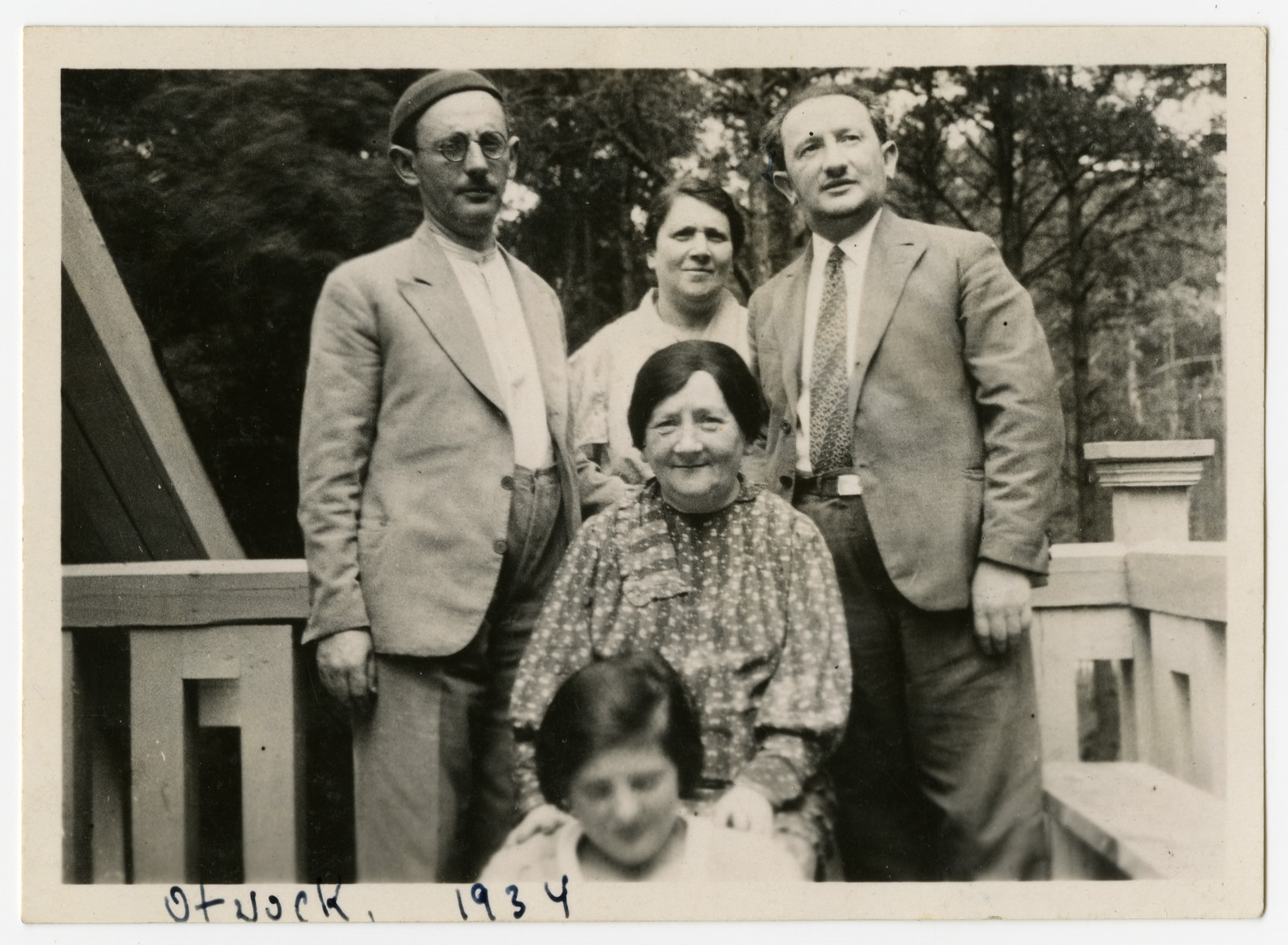 Miriam Rabinowitz sits on a porch surrounded by her children and granddaughter.   In the front is Celinka Rabinowitz (Szyja's daughter).  Standing from left to right are Szyja, Doba (Szyja's wife) and Pinchas Rabinowitz.