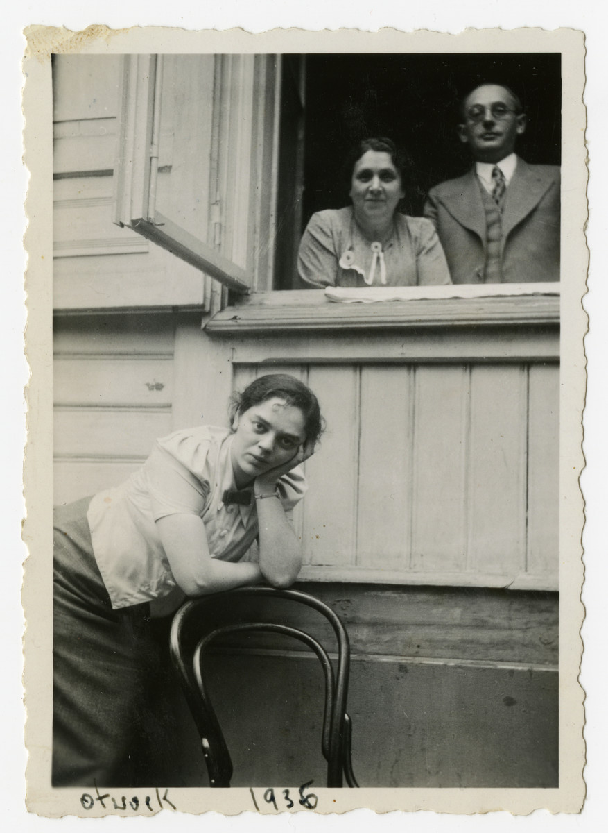Portrait of Rabinowitz family members at an open window.  Pictured looking out the window are Doba and Szyja Rabinowitz; in front is their daughter (?) Celinka.