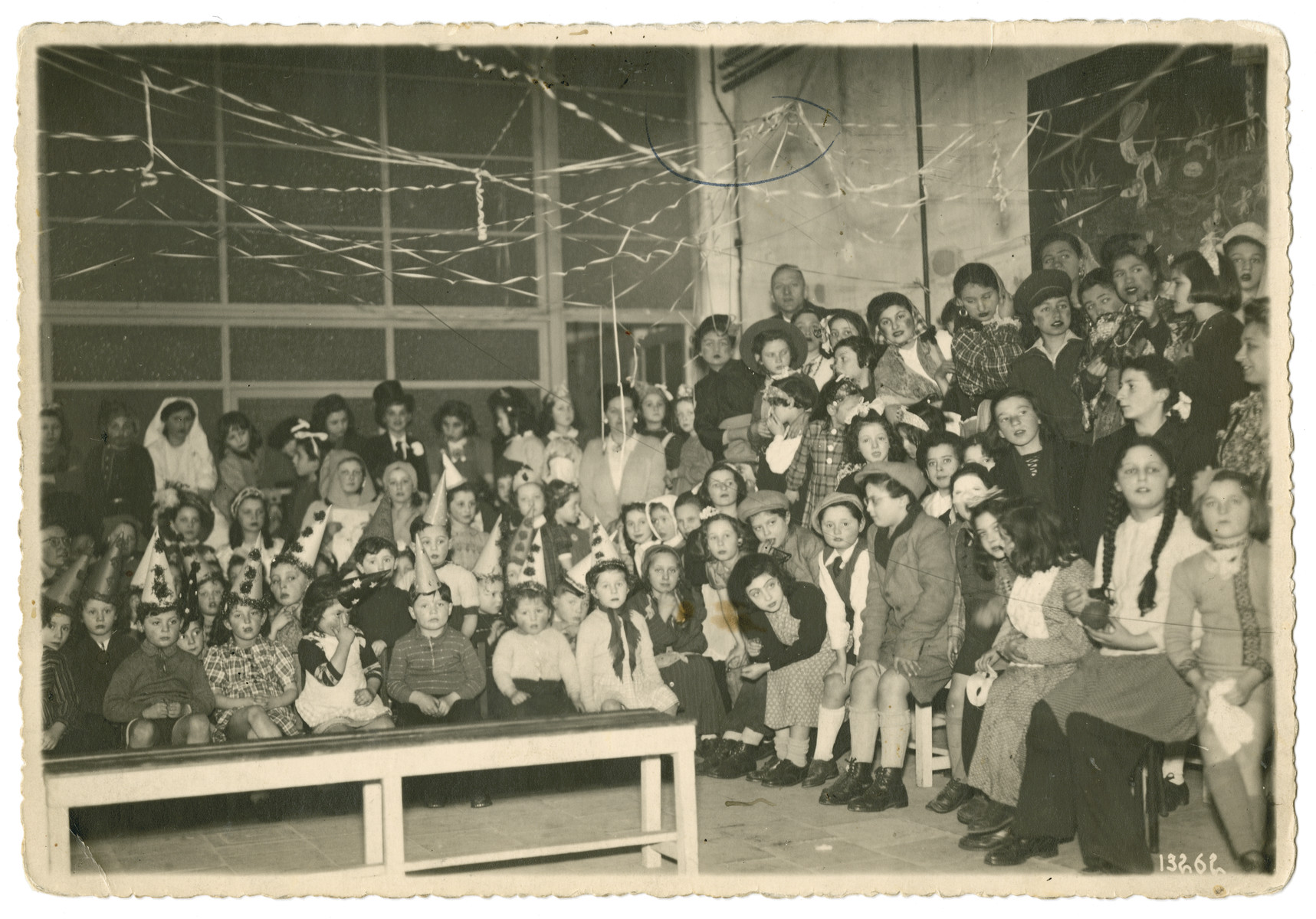 Group portrait of children, some wearing costumes, in the Yesodei HaTorah school in Antwerp.  Eva Schonberg is pictured in the front row, leaning over, in a dark sweater. Next to her on the right is Friedi Teitelbaum.  To the left of Ava is Astrid Freudman.  Pictured third from the left wearing a hood is Evelyn Goldenberger.
