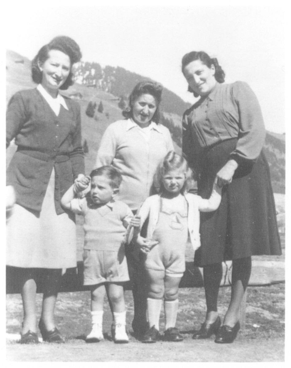 Jewish women and their children pose outside in the Morgins refugee camp.  Roza Schonberg is on the far right holding the hand of her daughter Alice.  Pictured on the left is Willy Lipschitz holding hands with his mother.