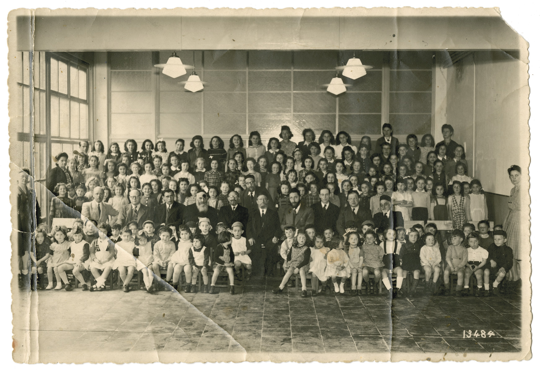 Group portrait of children in the Yesodei HaTorah school in Antwerp.  Eva Schonberg is pictured in the 6th row, third from the middle (to the right).