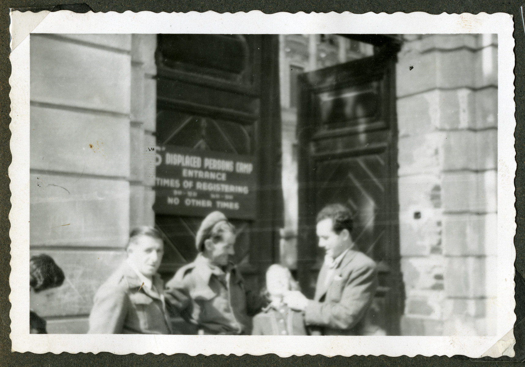 Rosian Bagriansky kids around with British soldiers outside the entrance to a building in the Graz displaced person's camp.