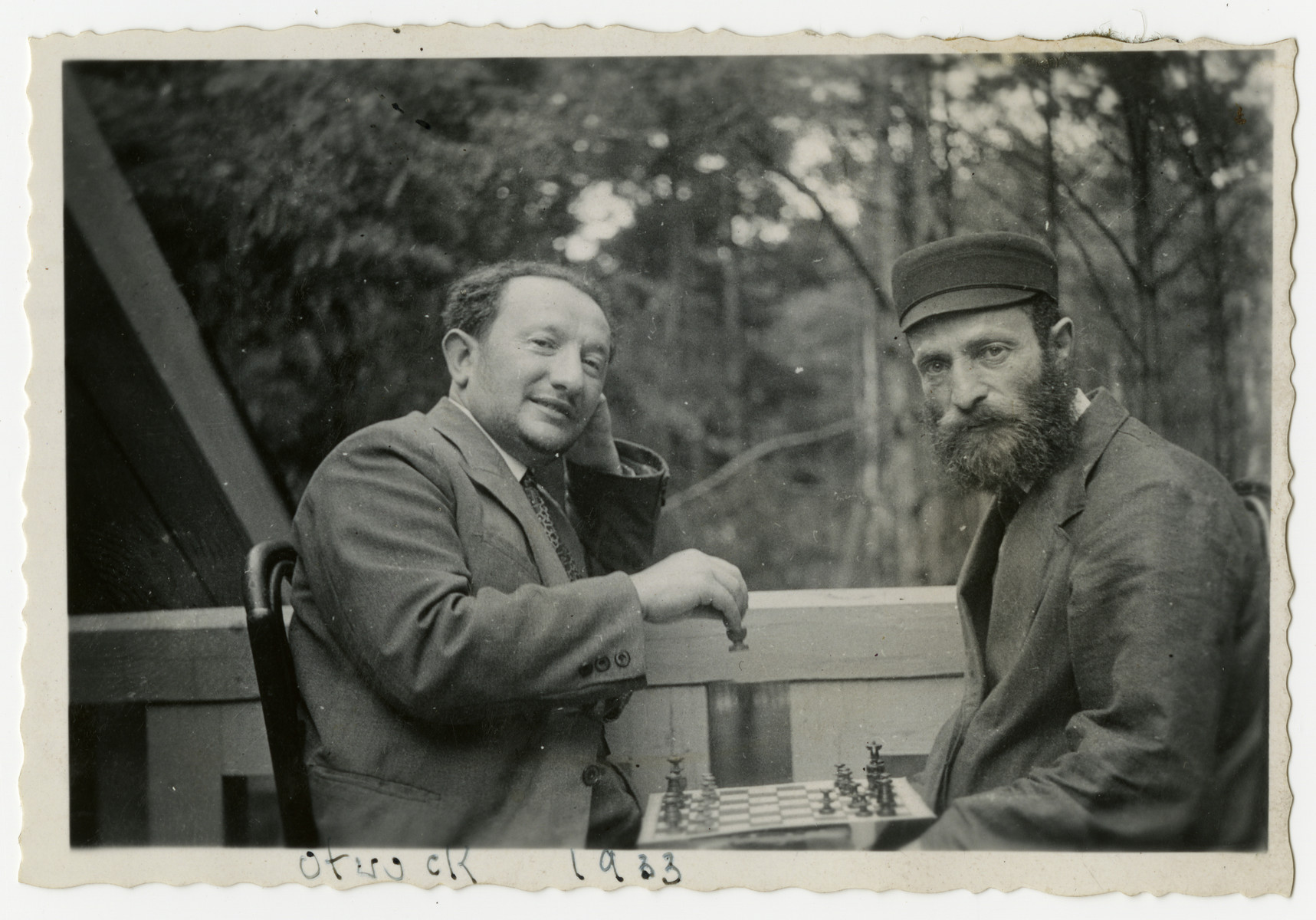 Two Jewish men play chess outside on a veranda.   Pictured on the left is donor's uncle Pinchas Rabinowitz.