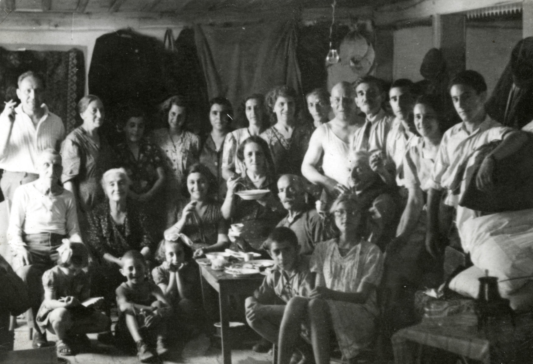 Jewish families crowd into temporary living quarters in the balcony of the synagogue in Haskovo.  Reine Behar is on the bottom right.  Her father is standing behind her.