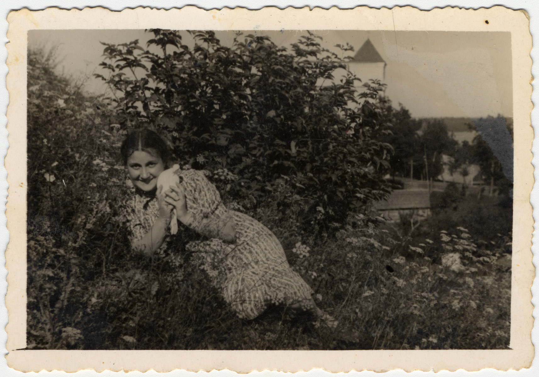 Sonia Boldo lies in a flower bed holding a kitten in prewar Nowogrodek.  Sonia escaped from the Nowogrodek ghetto in 1942 and came to the forest.  There she met and married Zus Bielski.