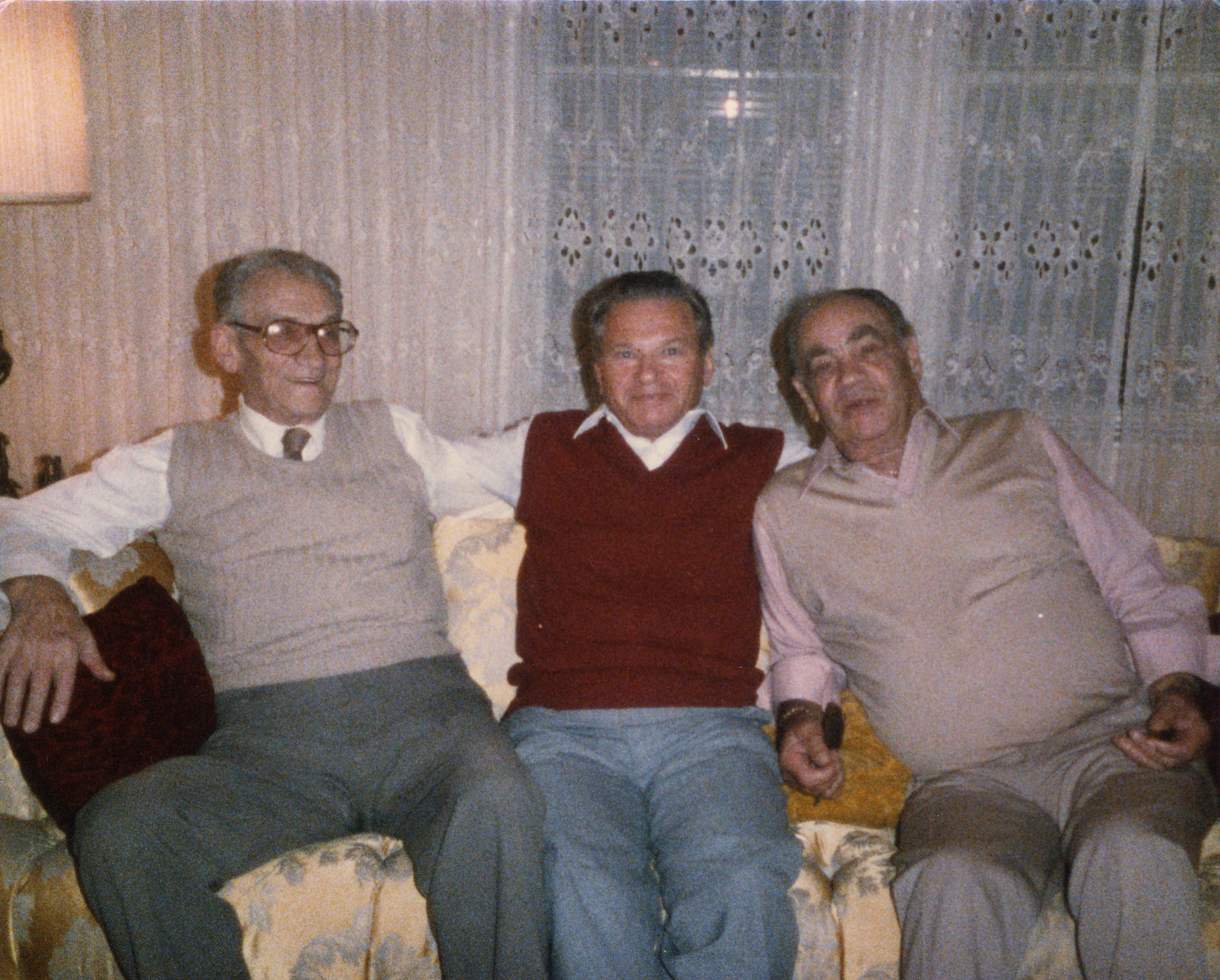 The Bielski brothers pose on a couch with a friend.  Tuvia Bielski is on the left and Zus Bielski is on the right.