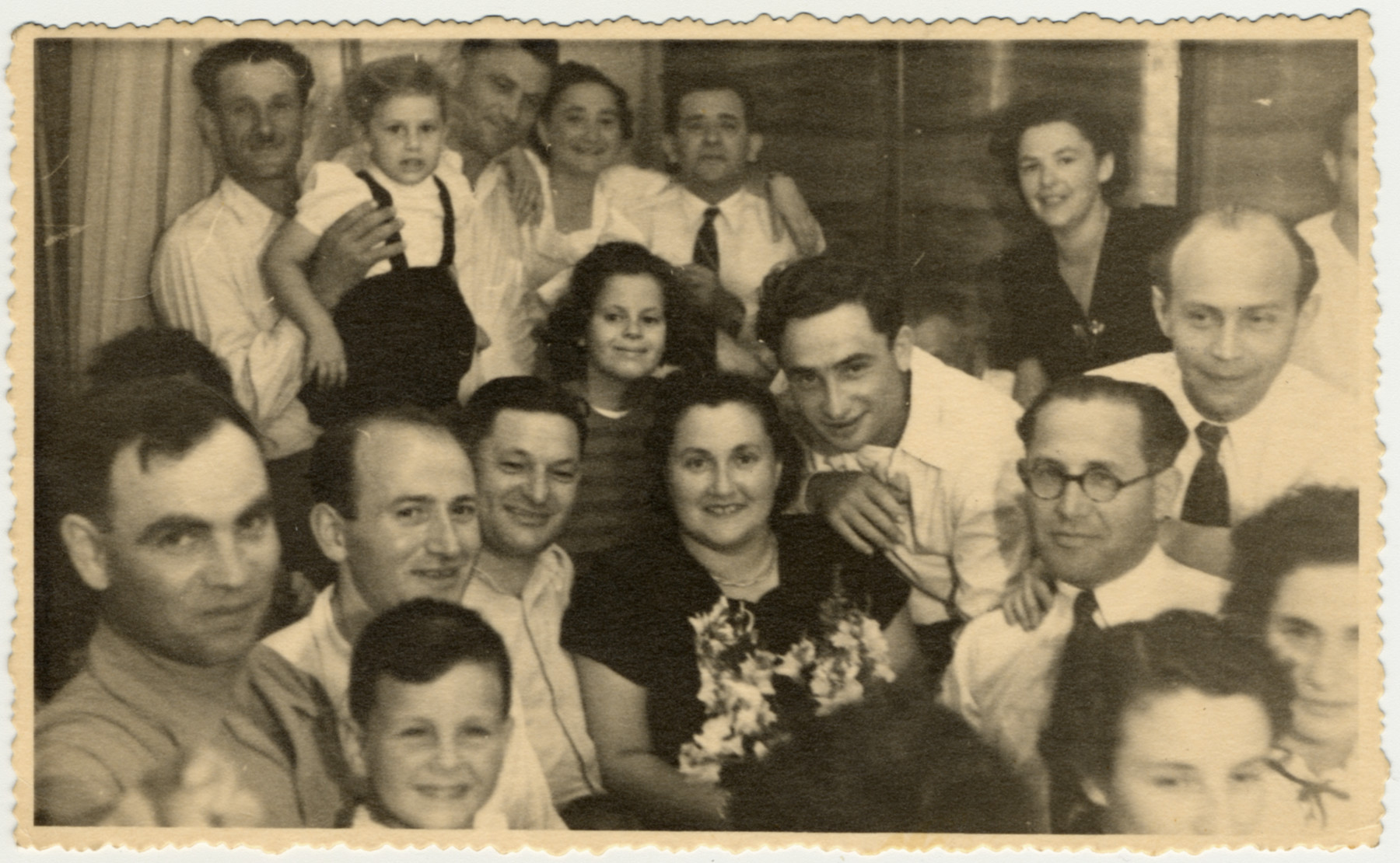Former Bielski partisans gather for a celebration in Palestine.  Zus Bielski is pictured at the bottom left with his son Yakov.  Sonia Bielski is in the center holding the flowers and Aron Bielski is leaning up against her.  Also pictured are left Yehuda Bell (Bielski) first cousin, his daughter Neelie (now known as Leslie Bell), Dr. Henry Pinsky and his with Genya. Far right top, Raya Kalmanovitz (secretary of the Bielsky group).