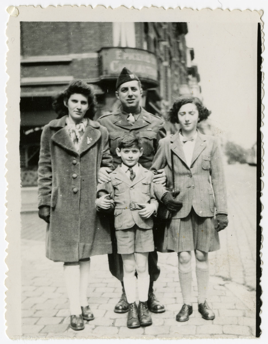Three Belgian Jewish children pose with an American soldier shortly after liberation.  From left to right are Rosa Markowicz, Cpt. Mathew Kleinman (a cousin by marriage), Charlotte (Lotti) Horowicz (cousin of the donor who also survived in hiding) and Harry Markowicz in front.