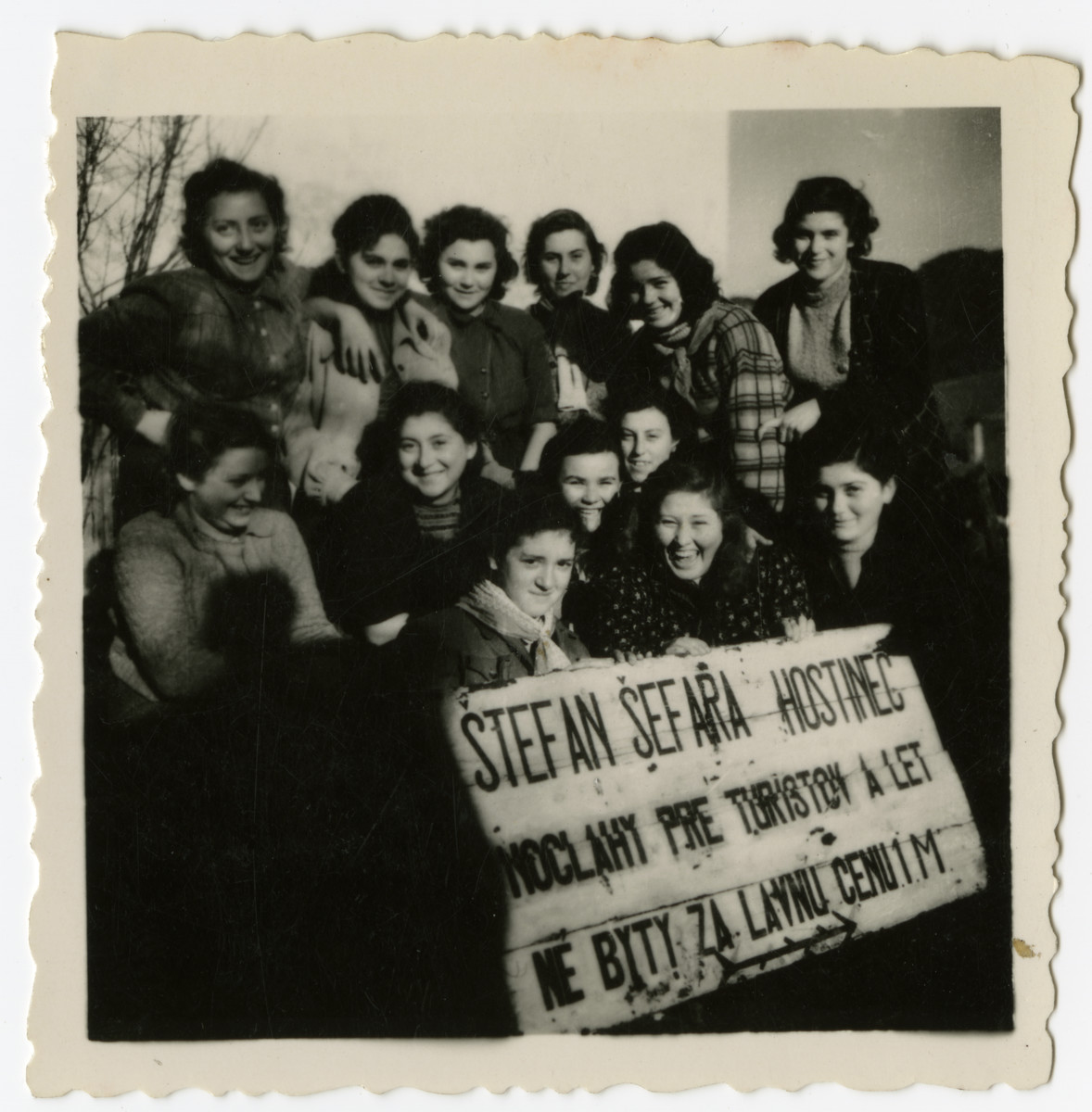 """A group of Polish Zionist youth go on an excursion to Slovakia.  Fela Liwer is in the second row on the far left.  The girls are holding a sign that reads:  """"Stefan Sefara inn/guesthouse overnight stays for tourists and holiday homes for a cheap price 1 M(eter)"""""""