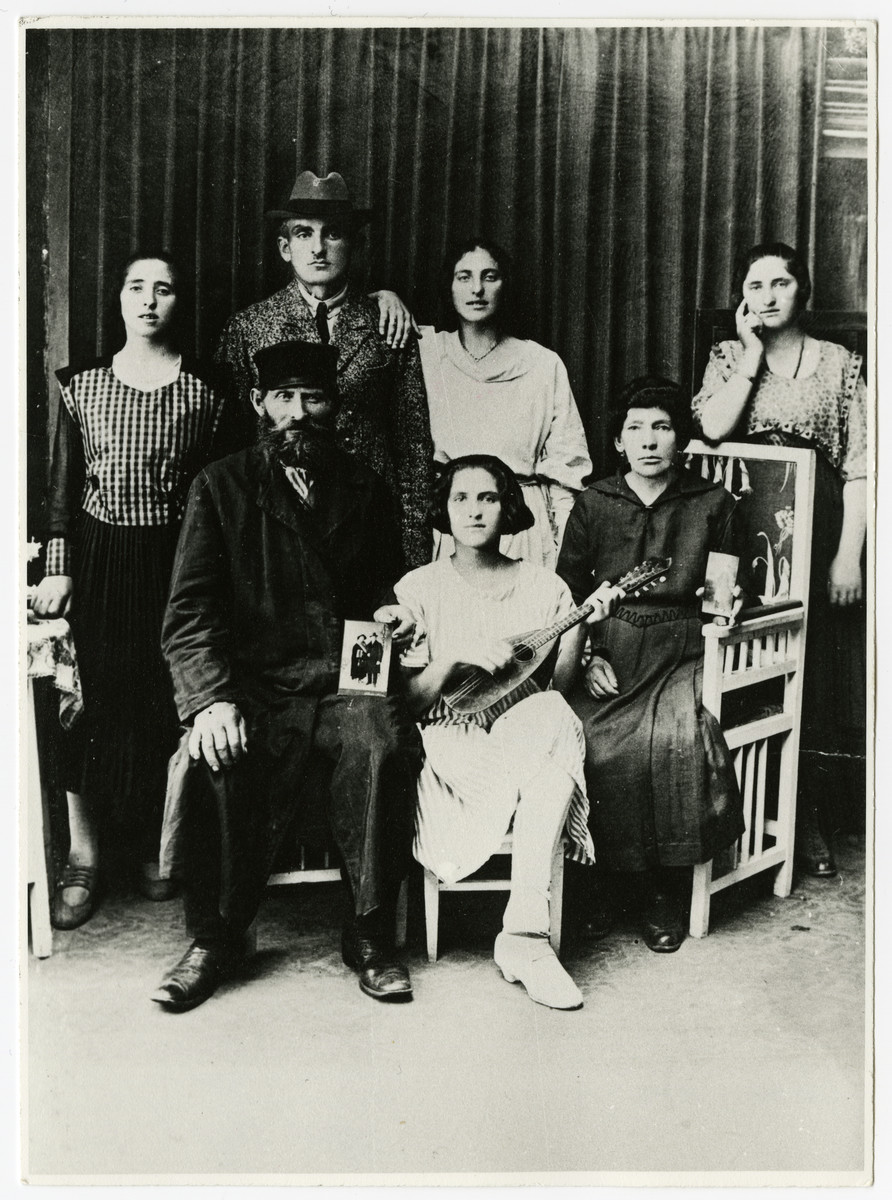 Leiser and Hindll Reisl pose for a studio portrait with four of their seven children; they hold photographs of two of the missing children.   Pictured are Feigl Nussbaum and her husband Klapper Nussbaum, Taube Chane, Mania, Leiser (father) Edith, and Hindle Reisl (mother).  Leiser holds picture of Jacob and his wife Paula.  Hindl holds picture of Max (the father of the donor).