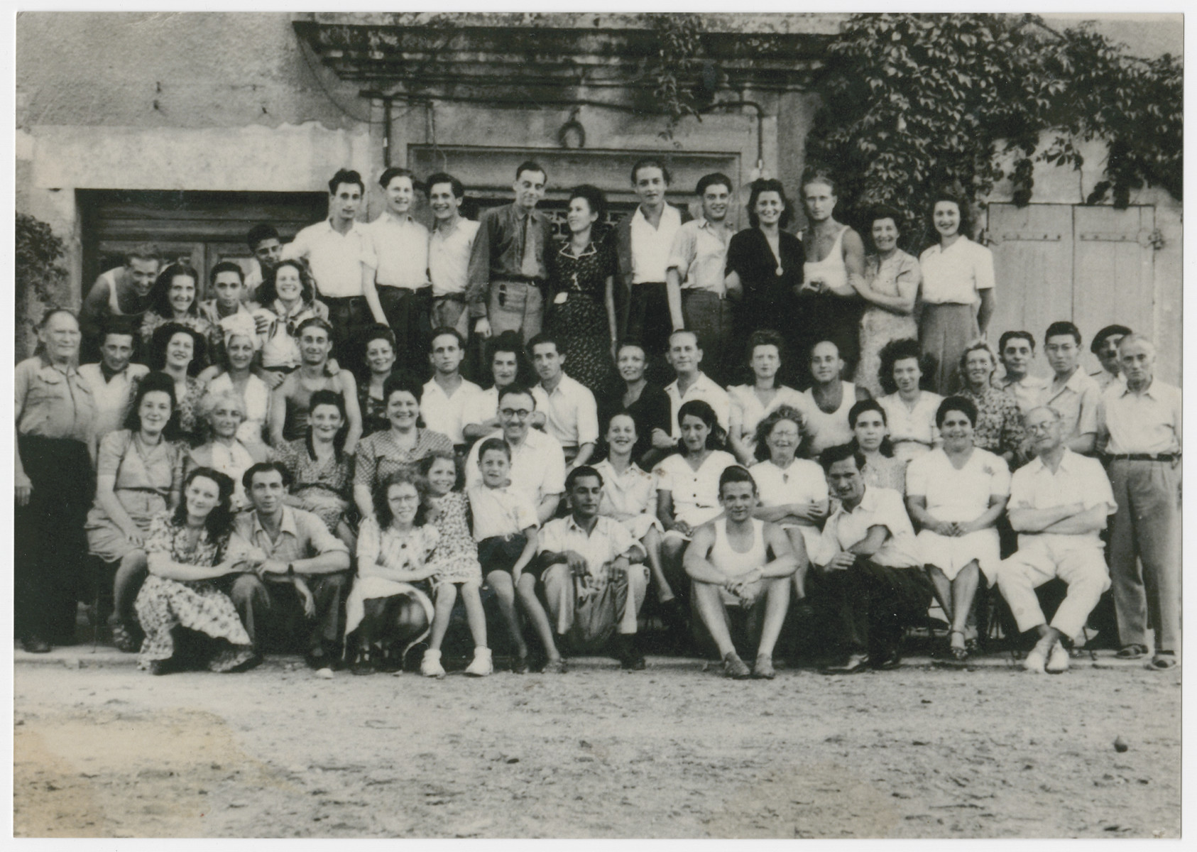 """A group of displaced persons poses for a group photograph, possibly at a monastery near Munich.  Among those pictured is Helen Martel (second row, first from left).    The inscription on the back of the photograph reads, """"Papiezka."""""""