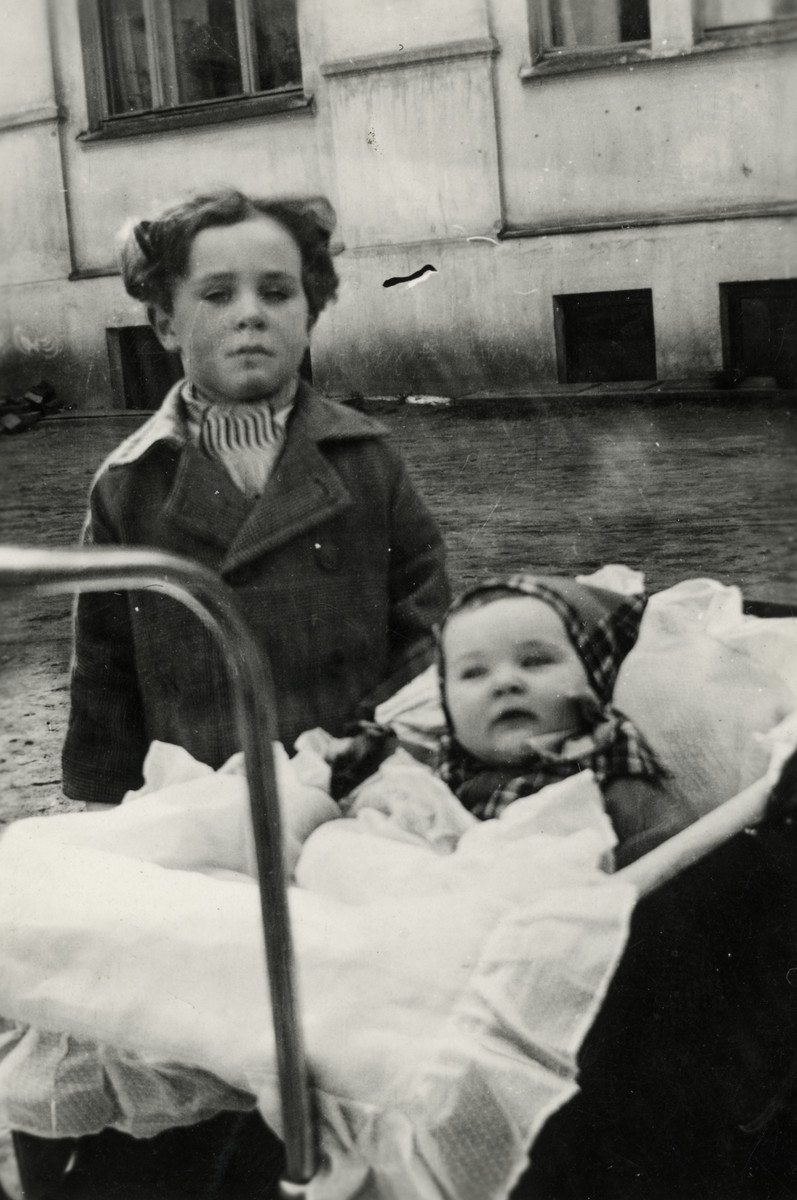 Shalom Kaplan stands next to his sister Yehudit who is in her baby carriage.