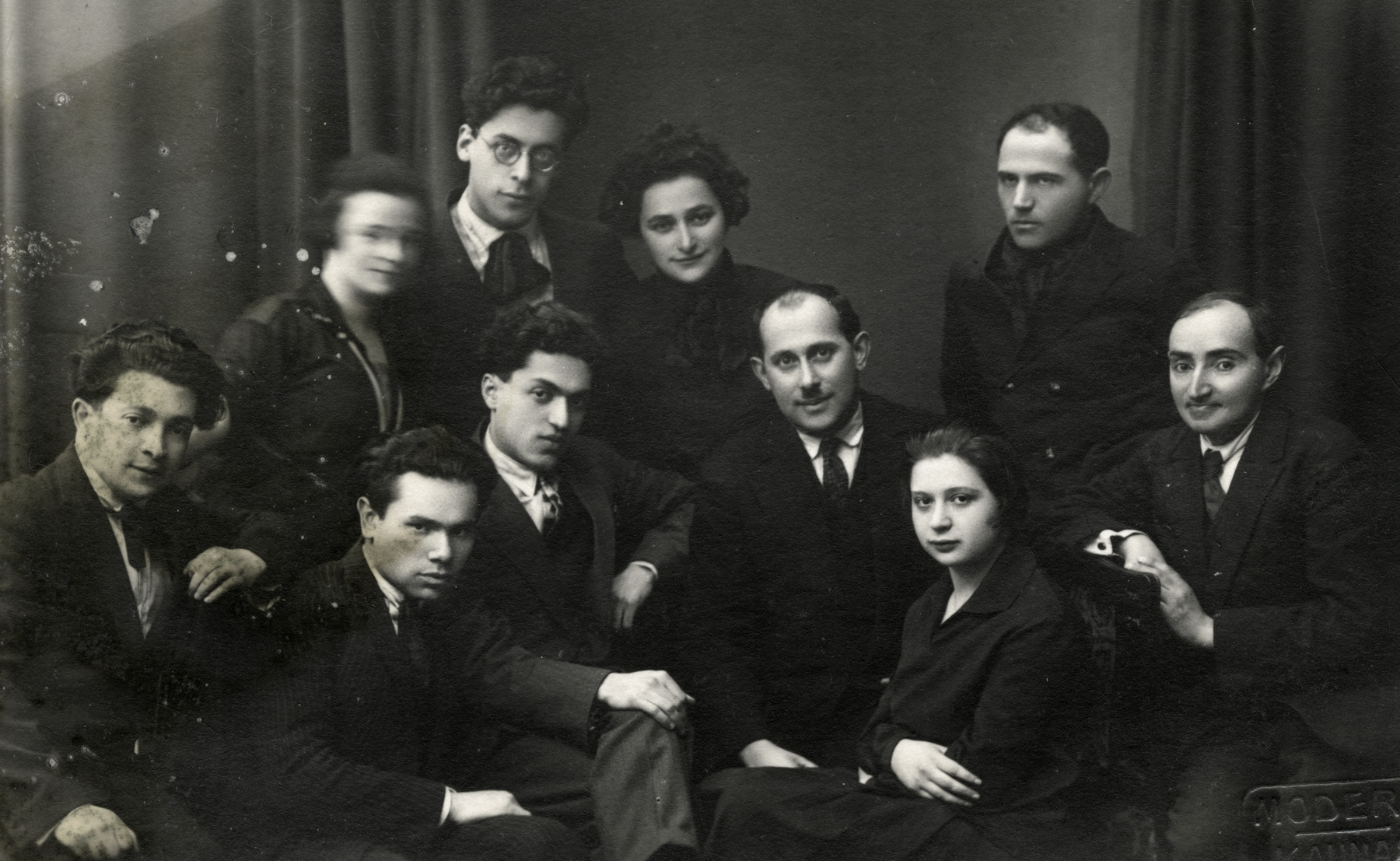 A group of young Jewish intellectuals in Kaunas gathers for a going away party for David Frum who is immigrating to South Africa.  Front row (right to left): Kalman Zingman (editor of Vispa), father of Avraham Zimrani, Batia Prakar (dentist), Mordechai Yaffa (poet), Yaakov Lipshitz (artist), Aharon Goldblat (poet).  Standing: Zeli Boker (artist), Leah Greenstein (poet), Szeinson (artist), Shein.