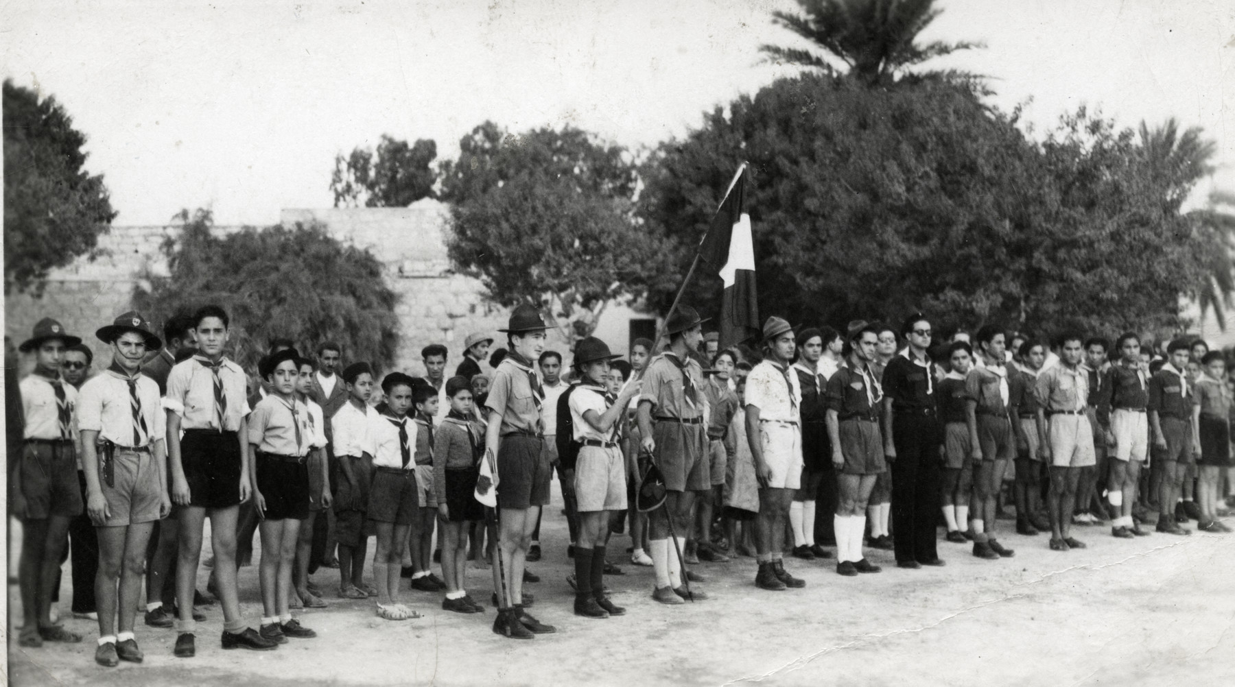 Children stand at attention during a flag raising ceremony at the Ayindram Betar summer camp.
