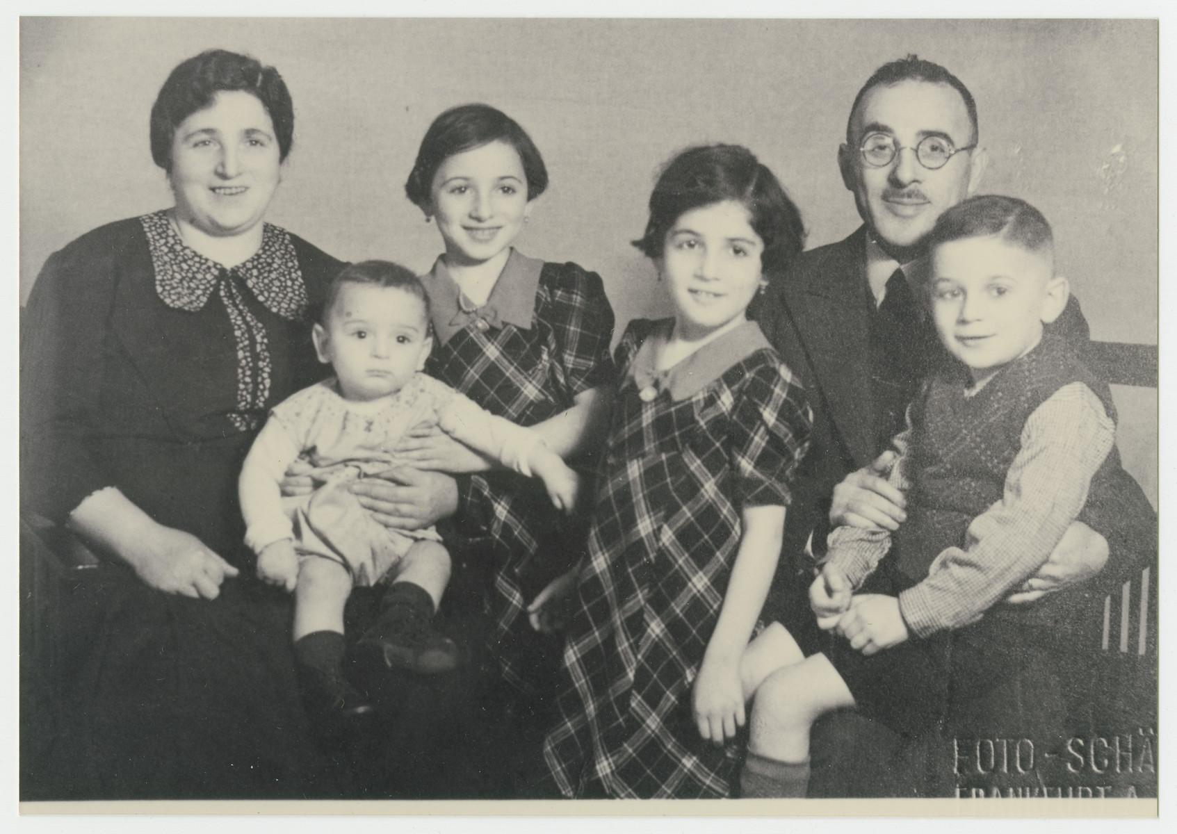 Portrait of the Oppenheimer family taken before the three older children left Germany for France.  Pictured from left to right are Frieda holding Eli, Mini, Miriam, Hermann and Karl Oppenheimer.