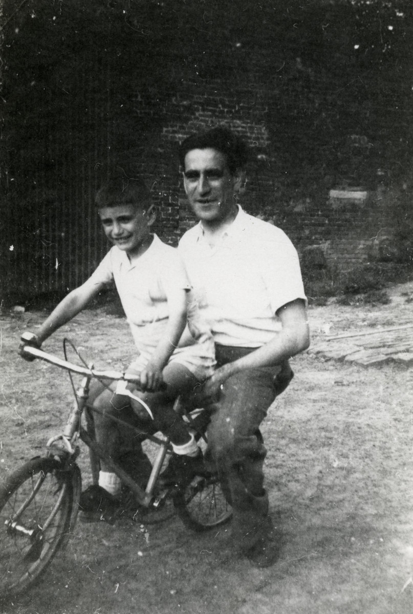 Abusz Werber rides a bike with his son Michel shortly after liberation.