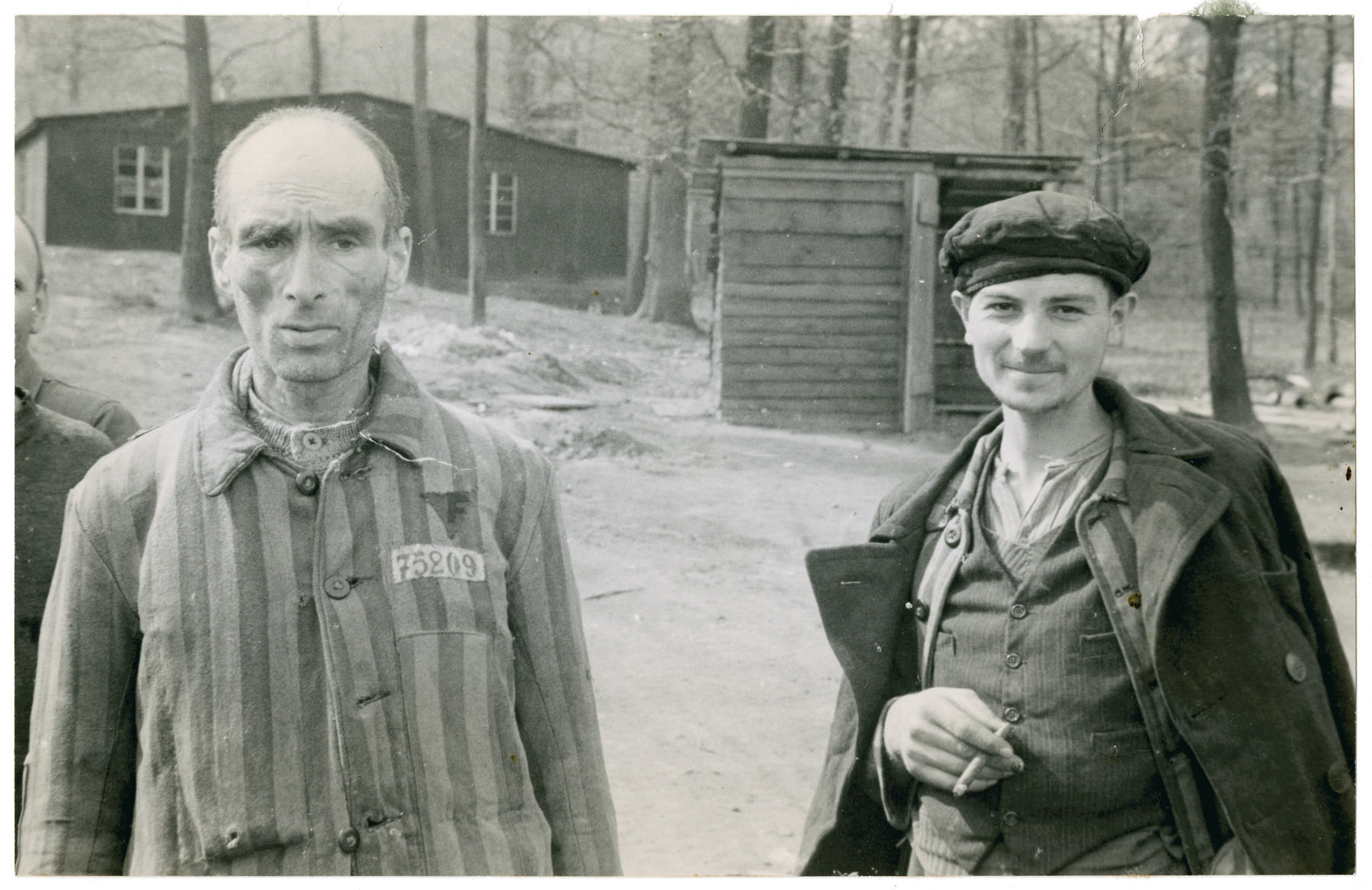 Two survivors stand outside a barrack of the Langenstein-Zwieberge concentration camp.
