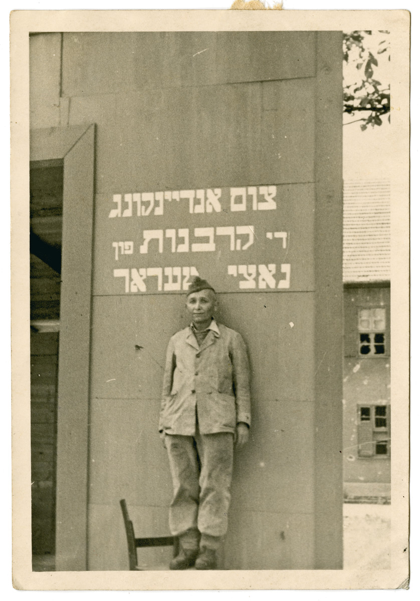 "A young Jewish displaced person poses [perhaps in his camp uniform] in front of a memorial to the victims of the Holocaust.  The Yiddish memorial reads: ""As a memory to those sacrificed to Nazi terror."""