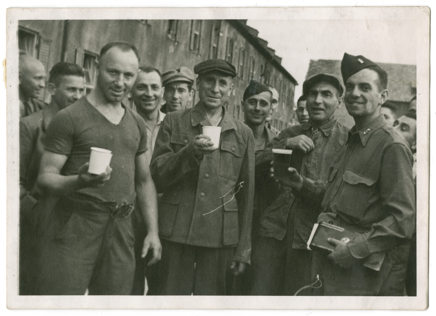 Survivors of a Kaufering camp [perhaps Landsberg] pose with American soldiers after liberation.