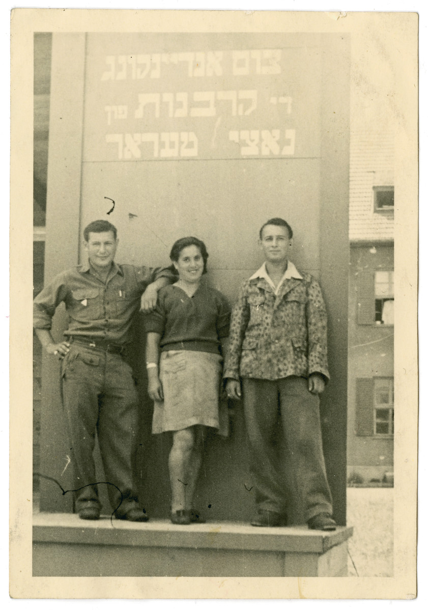 "Three Jewish displaced persons pose in front of a memorial to the victims of the Holocaust.  The Yiddish memorial reads: ""As a memory to those sacrificed to Nazi terror."""