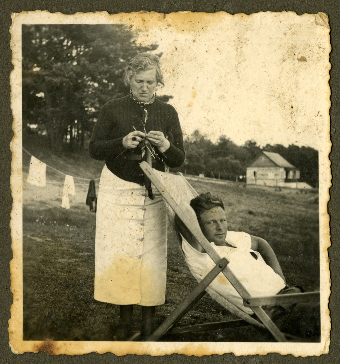 Paulius Bagriansky relaxes outside while Anna Blumenthal Chason knits.   This was taken in either Kacergine or Kulautova.