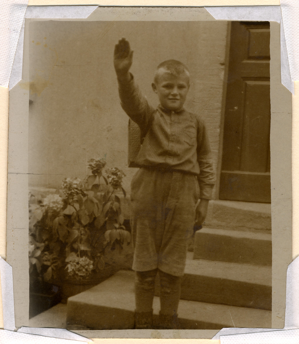A young boy gives a Nazi salute.