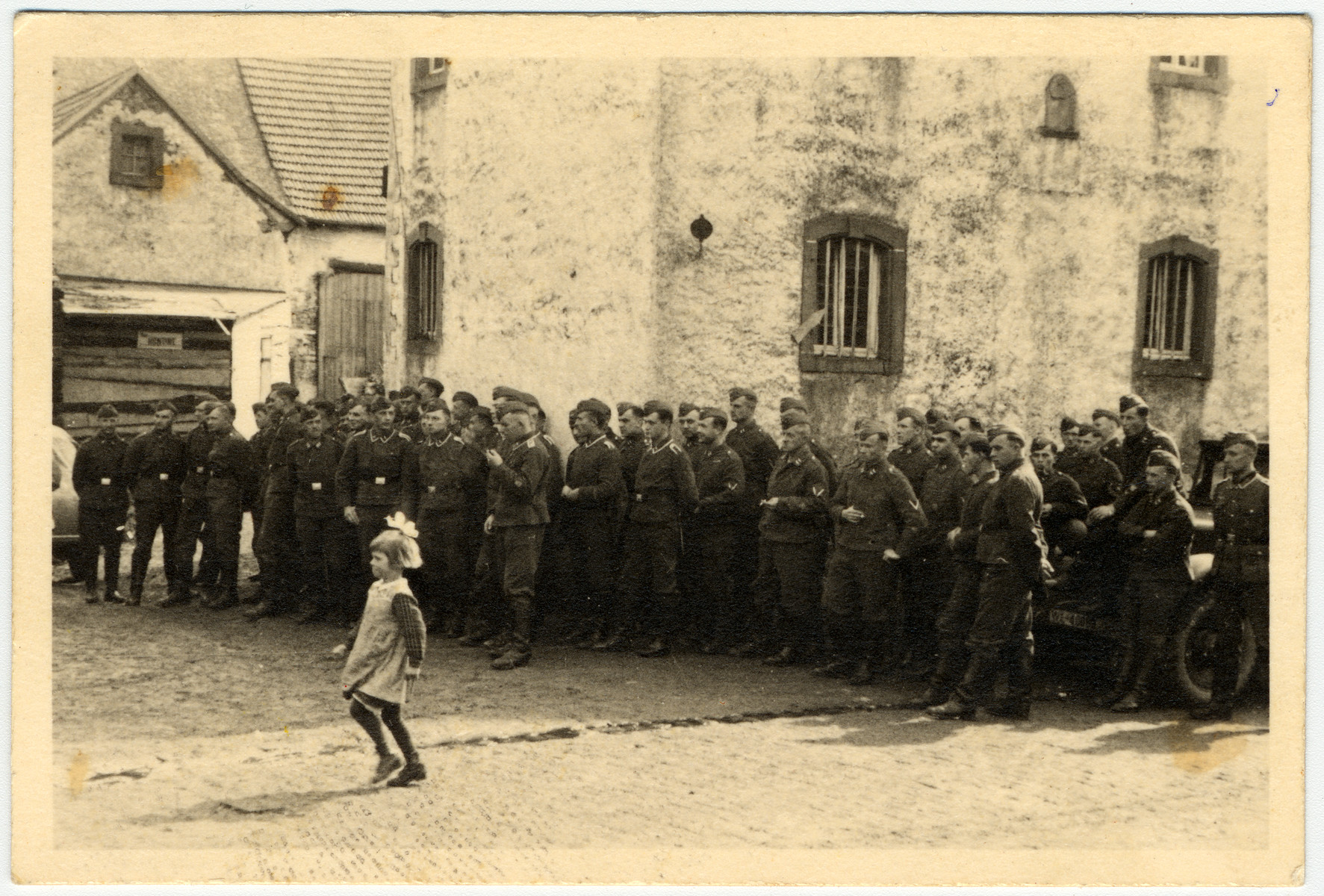 A young girl is pictured in front of a group of German soldiers.