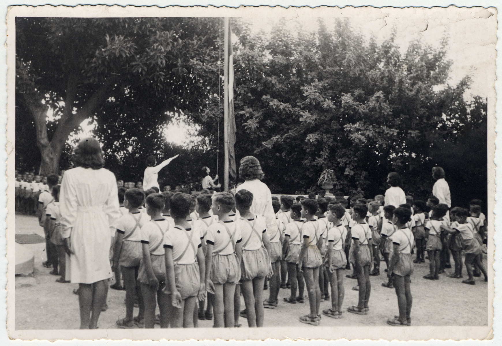 Young children led by young women stand at attention at a flag raising.  The leaders of the group give the Nazi salute.