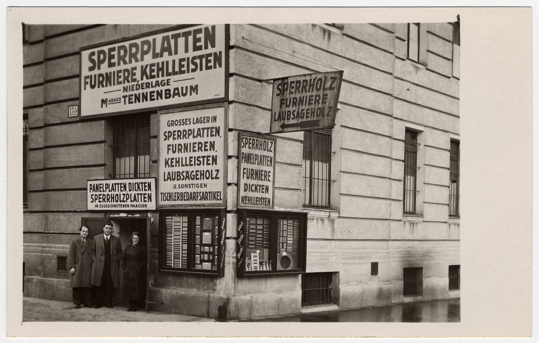 Mark Tennenbaum (middle), Hansel, and Deli Tetelbaum stand in front of Mark's warehouse in Vienna V Rechte Wienzeile 175.  The signs advertise items sold like plywood and veneer.
