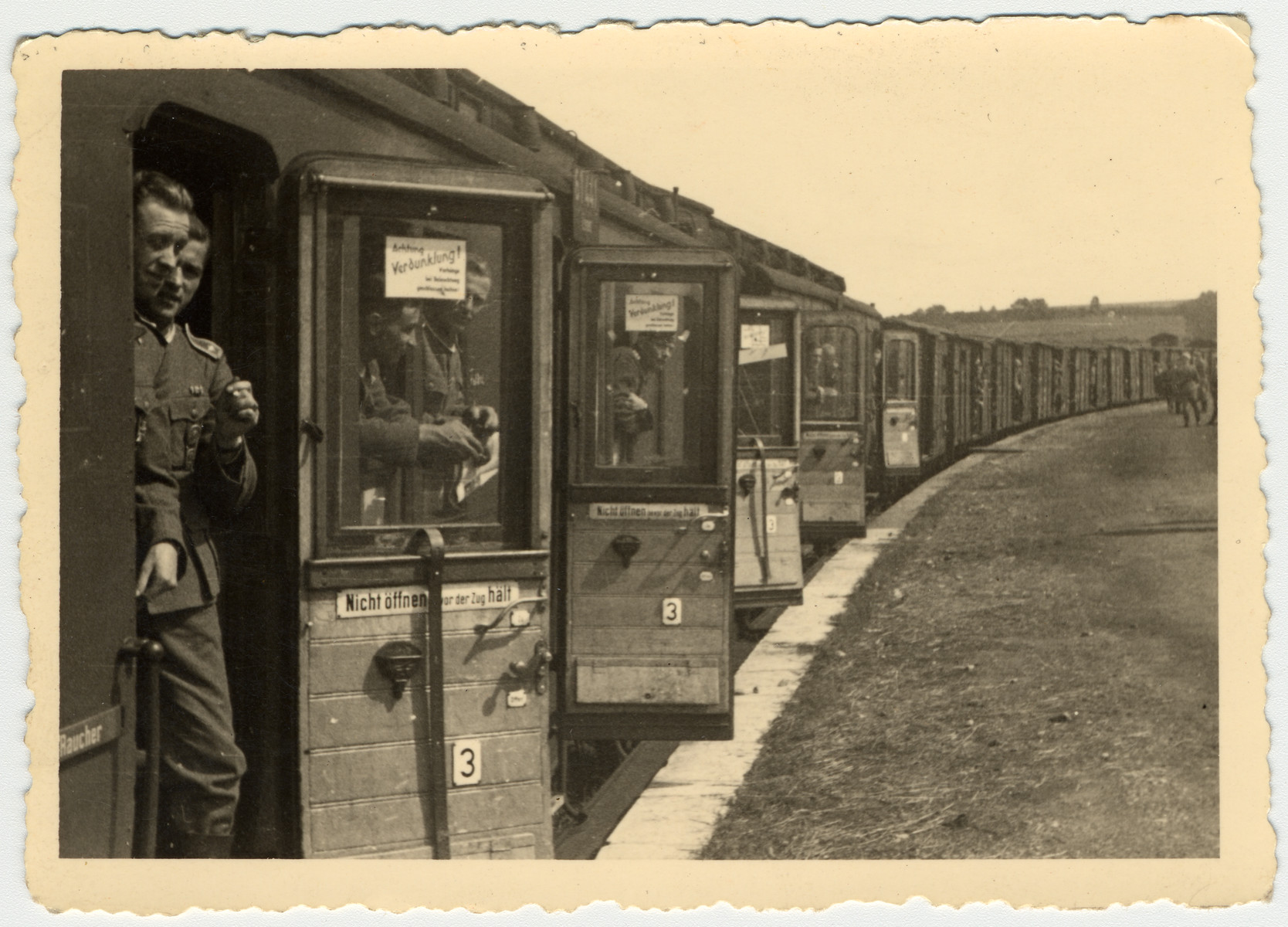 Members of the German military look out the door of a train.