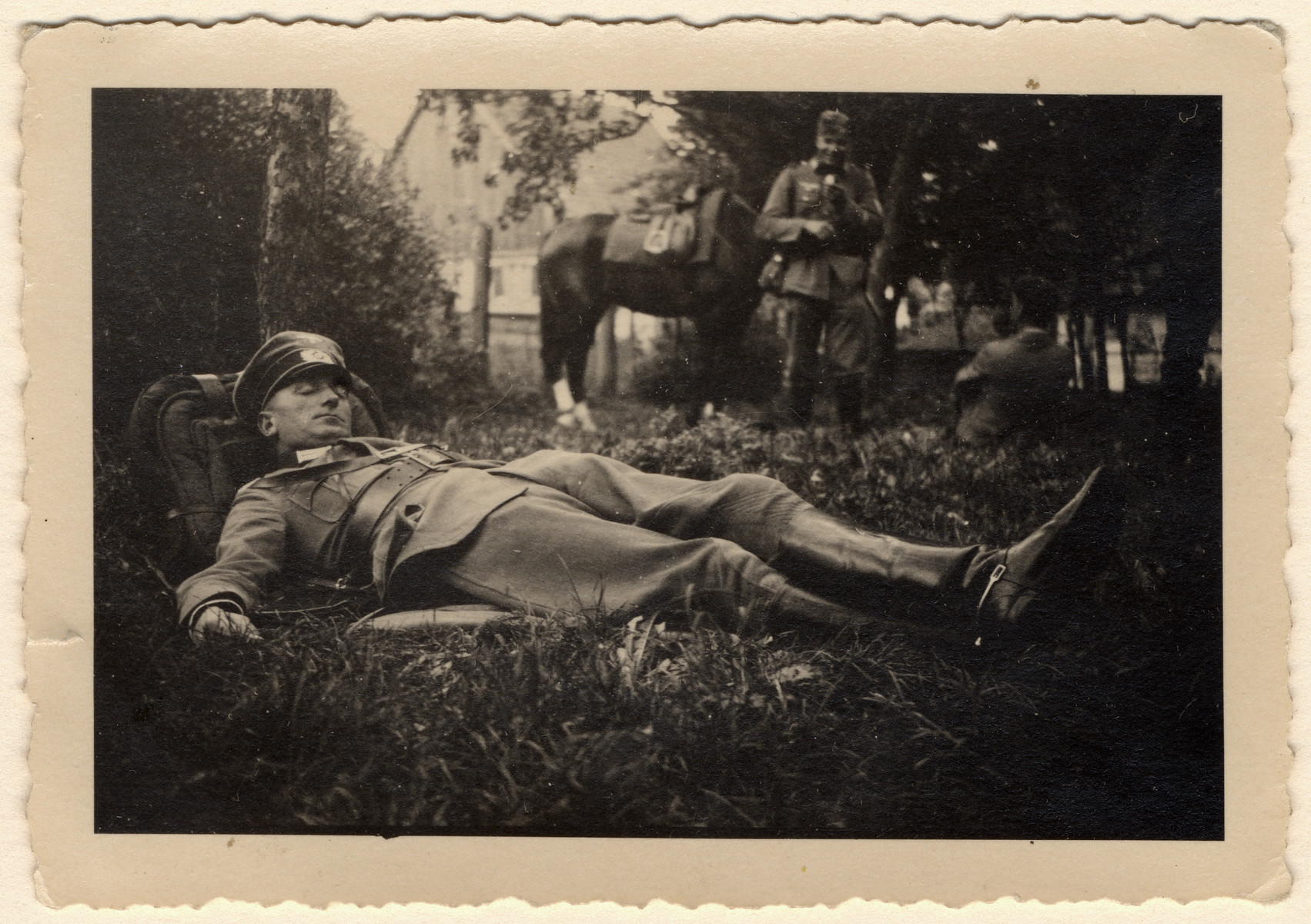 A soldier sleeps with his knapsack as a pillow.