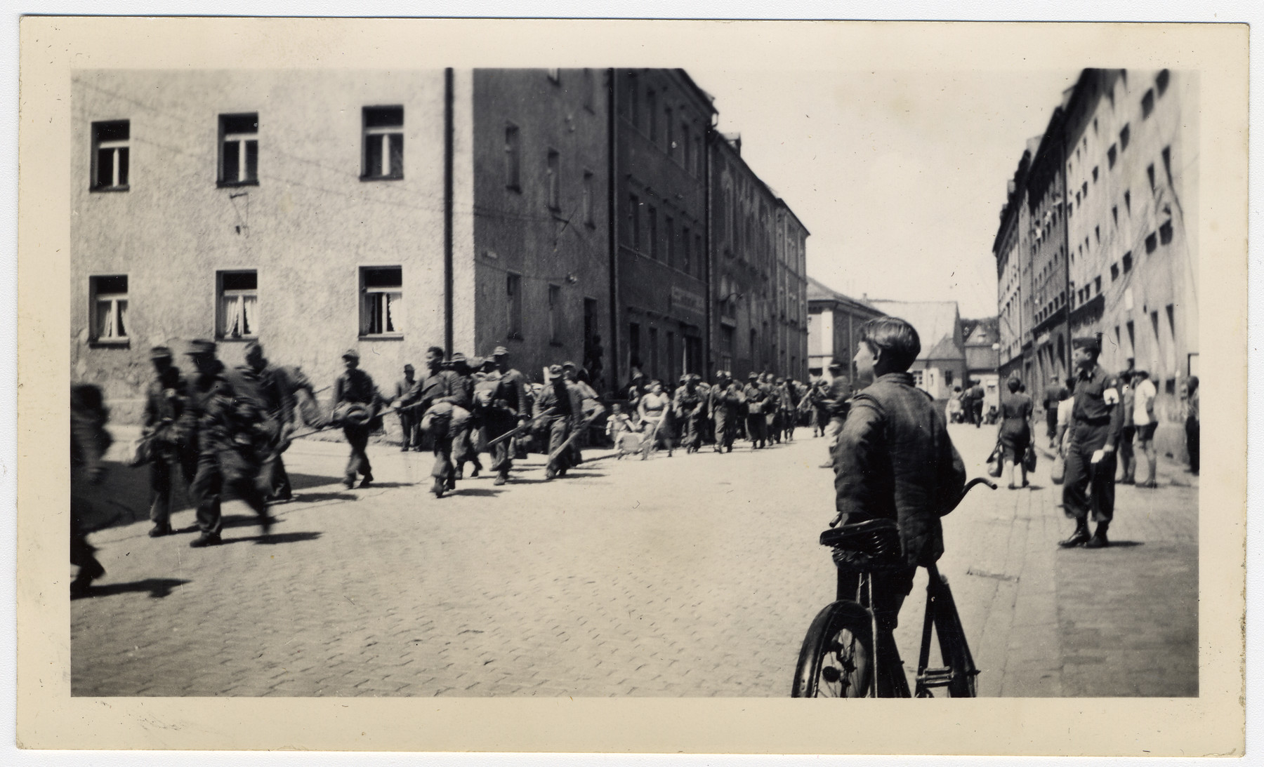 "German prisoners of war march under guard through Cham, a town in Bavaria  Original caption reads:  ""German P.W.'s marching thru Cham."""