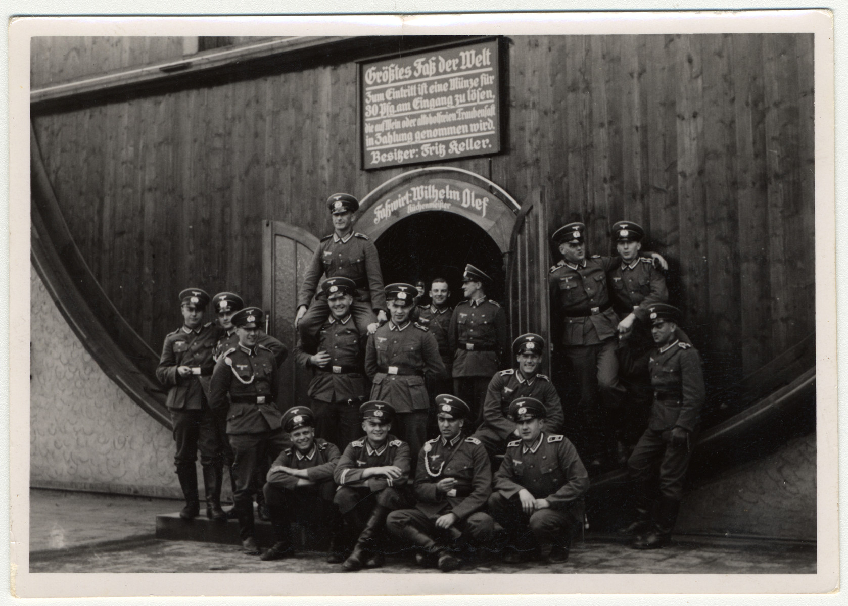 "German soldiers pose in front of a giant wine barrel.    The sign located above the soldiers reads:  ""Biggest Barrel in the World...For entry a token is to be purchased for 30 Pfennigs at entrance for which wine of alcohol-free grape juice may be taken in payment.  Owner:  Fritz Keller; Restaurant:  Wilhelm Olef, Master Chef."""