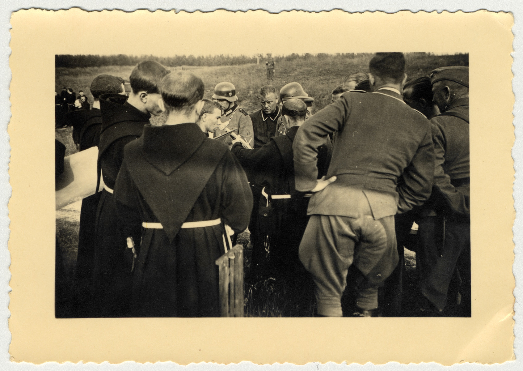 A group of monks gathers around some German soldiers.