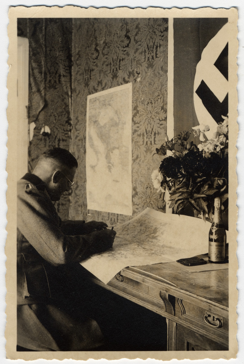 A German officer studies a map in his office.