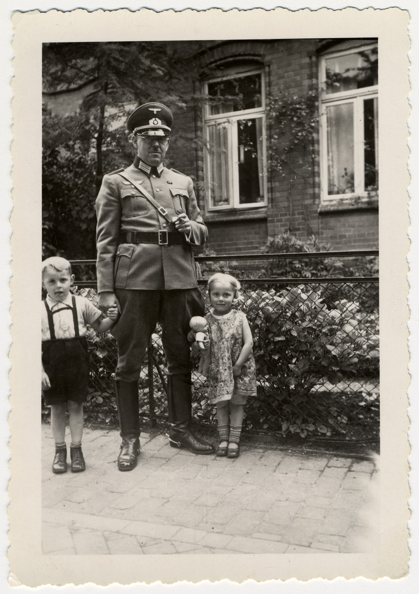 A German officer stands with two small children.
