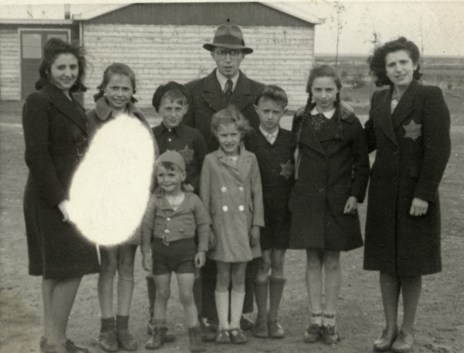 Portrait of the Birnbaum family in the Westerbork transit camp wearing Jewish stars on the street where they lived.  From left to right are an unidentified woman, Regina, Yaakov, Shmuel, Yehoshua, Suzy, Tzvi, Sonni and Regina Ohringer (a first  cousin who perished in Sobibor in 1943 at the age of 16).