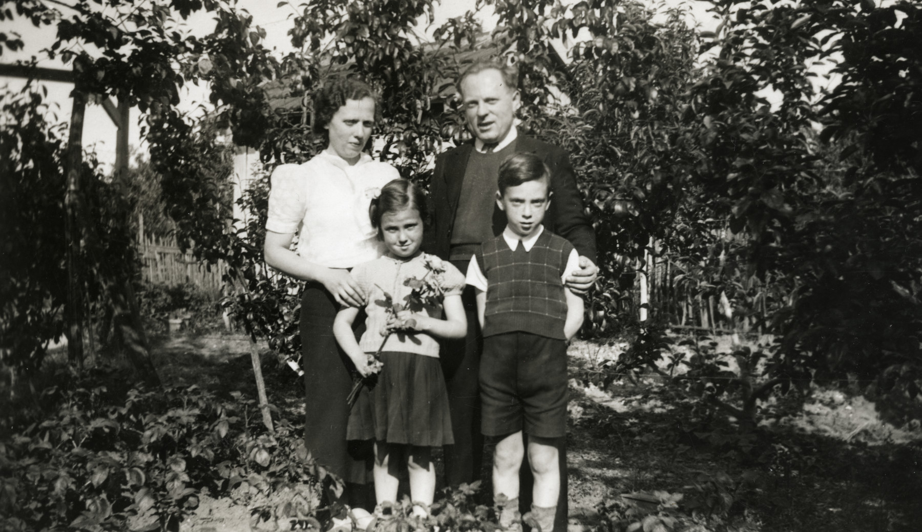 A Jewish family poses in the yard next to their home (possibly in Gagny).  Pictured are Rivka and Hersh Jakubovitch, with their children Fernande and Albert.