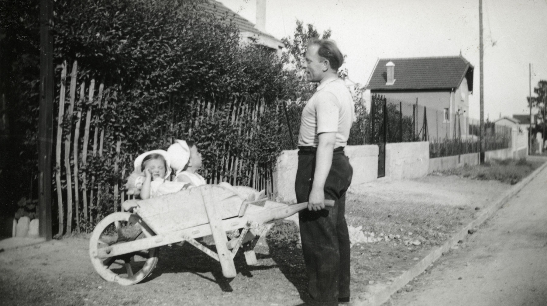 A Jewish father pushes his two young children in a wheelbarrow, near their home in Gagny, a suburb of Paris.  Pictured are Hersh Jakubovitch and his children Fernande and Albert.