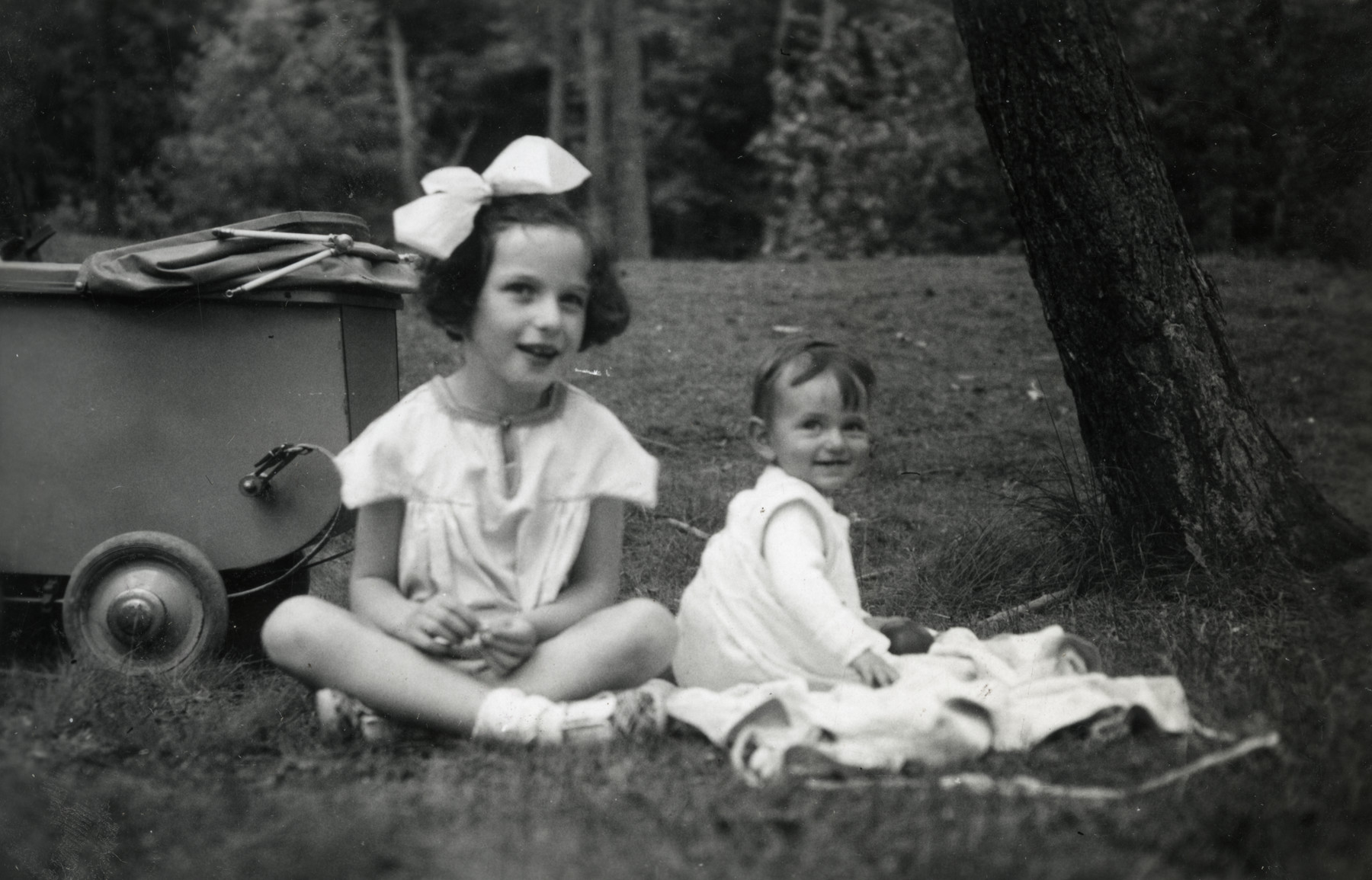 Two Jewish sisters sit on the grass next to a baby stroller.    Pictured are Henriette (left)  and Esther (right)  Mossel.  Esther is wearing a blouse brought back from her parent's visit to Palestine.