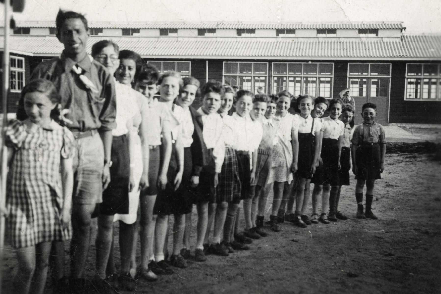 Children in a Jewish youth movement stand in formation in the Westerbork camp.  Sonni Birnbaum is on the far left and the group leader, Leo Blumemson, is next to her.