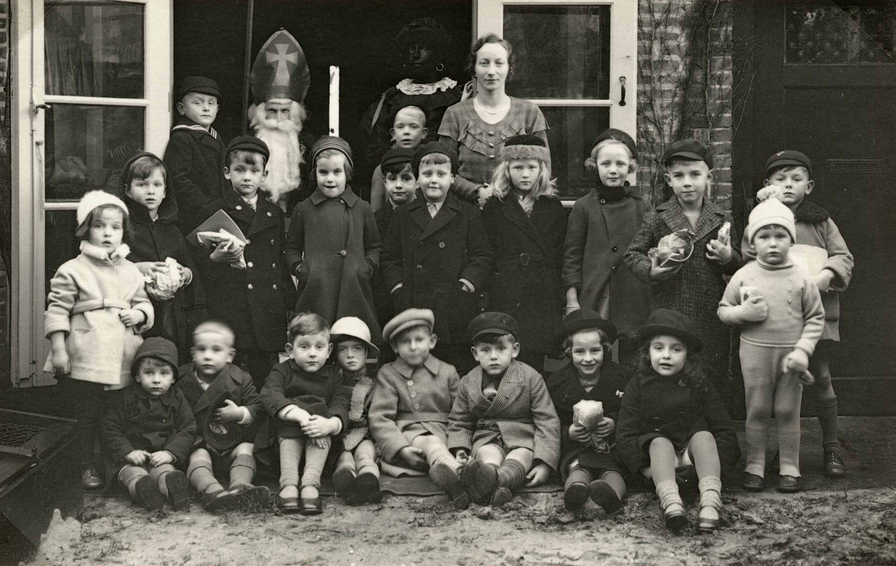 Group portrait of a kindergarten class with their teacher  celebrating Sinterklaas (St. Nicholas' Eve).    Among those pictured are Henriette Mossel (standing in second row, far left, in white coat), and men wearing the costumes of St. Nicholas and Zwarte Piet.