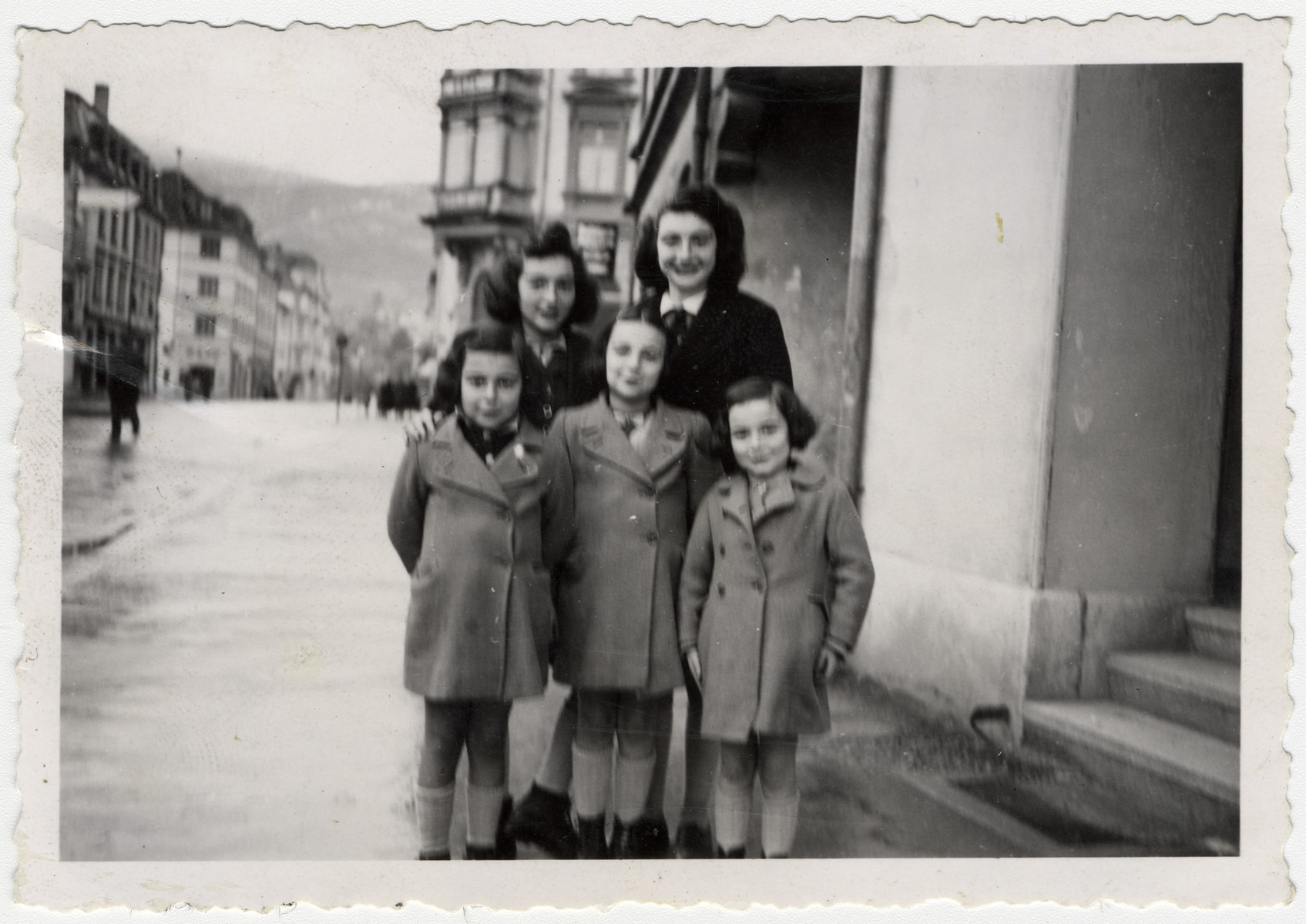 The five daughters of the Jewish lawyer and rescuer Matthieu Muller pose on a street [possibly in Paris].  Pictured left to right, bottom row: Edith (later Bloch), Judith (later Schwartzman), Noemi (later Schoenthal).  Top row: Miriam Muller (later Gross) and Florine Muller (later Klein).
