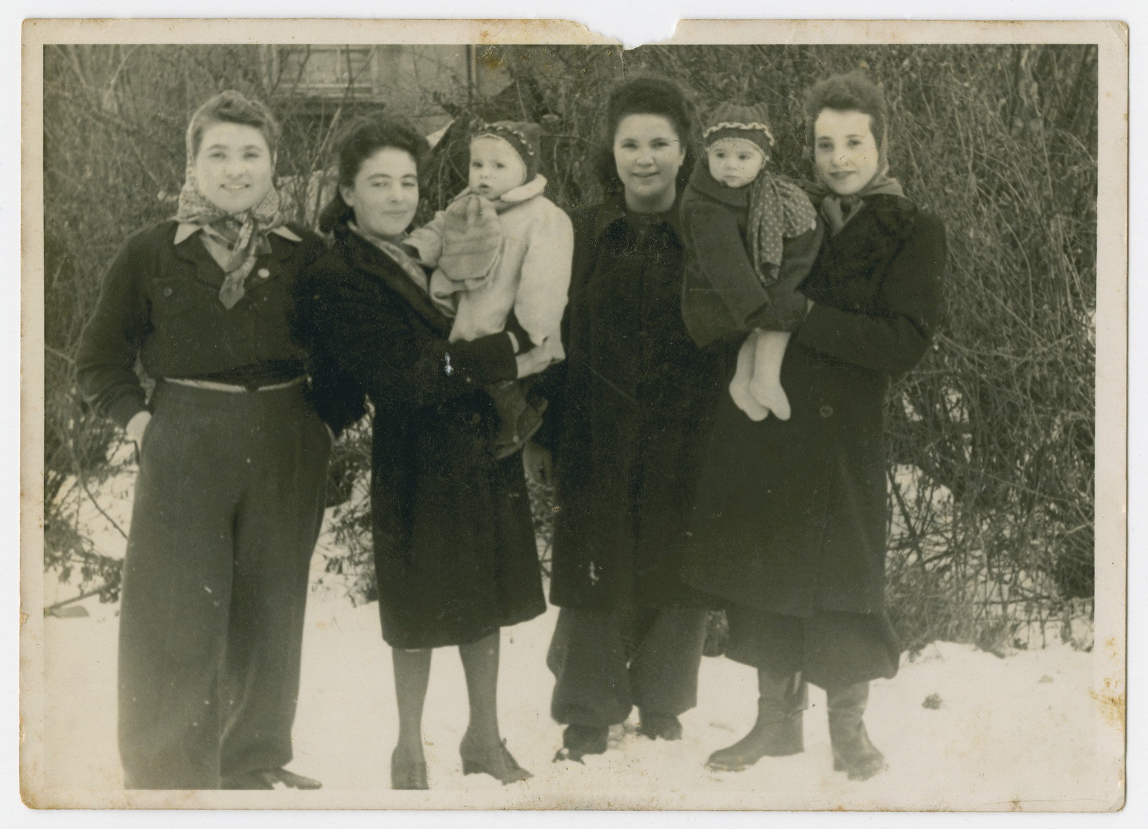 Group portrait of women, two of whom are holding their babies in the Eschwege displaced persons camp.  Pola Dichter, holding her daughter Klara, is second from the left.