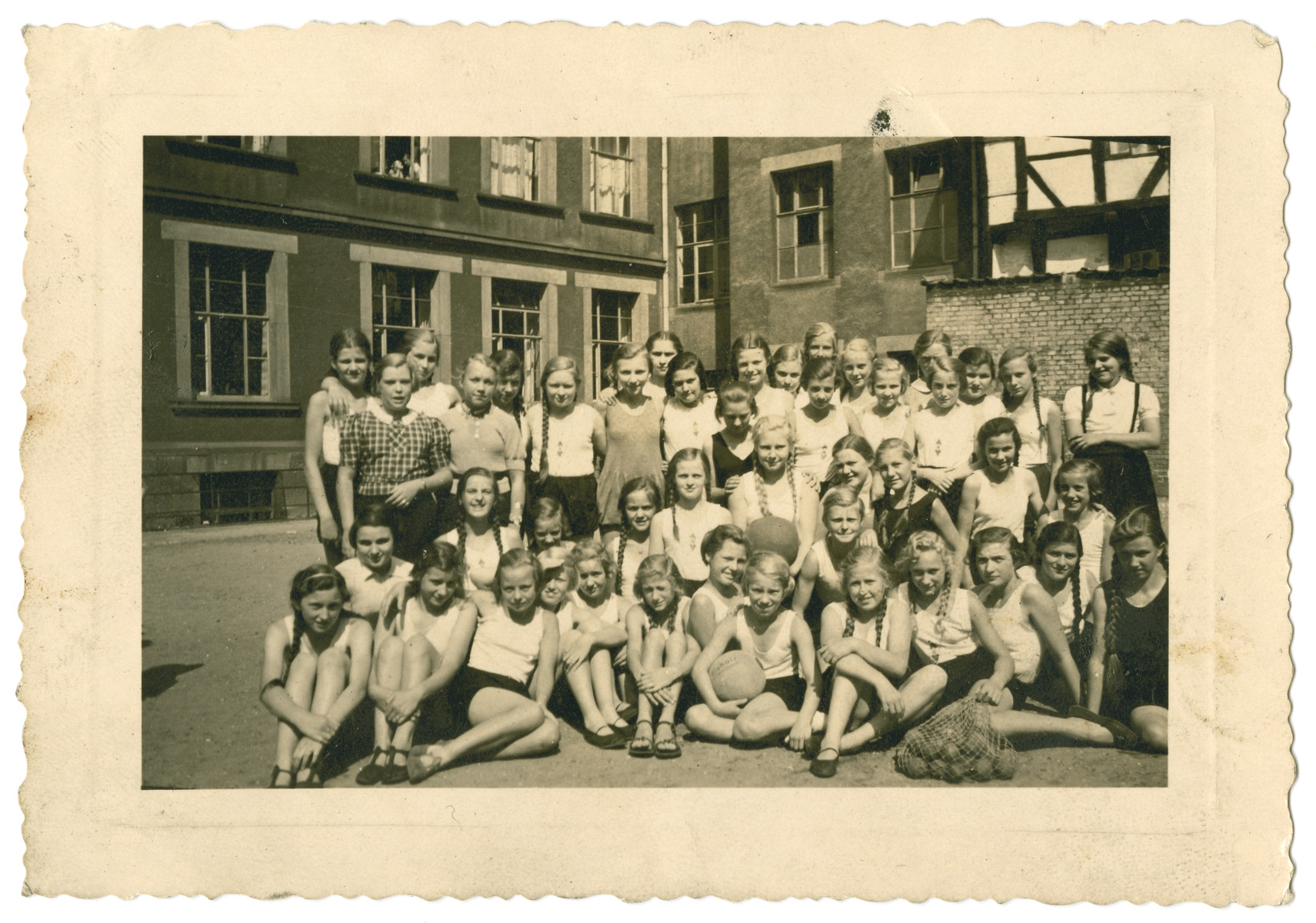 A group portrait of girls in a gymnasium schoool.   Doris Tager is in the first row (second from the left)