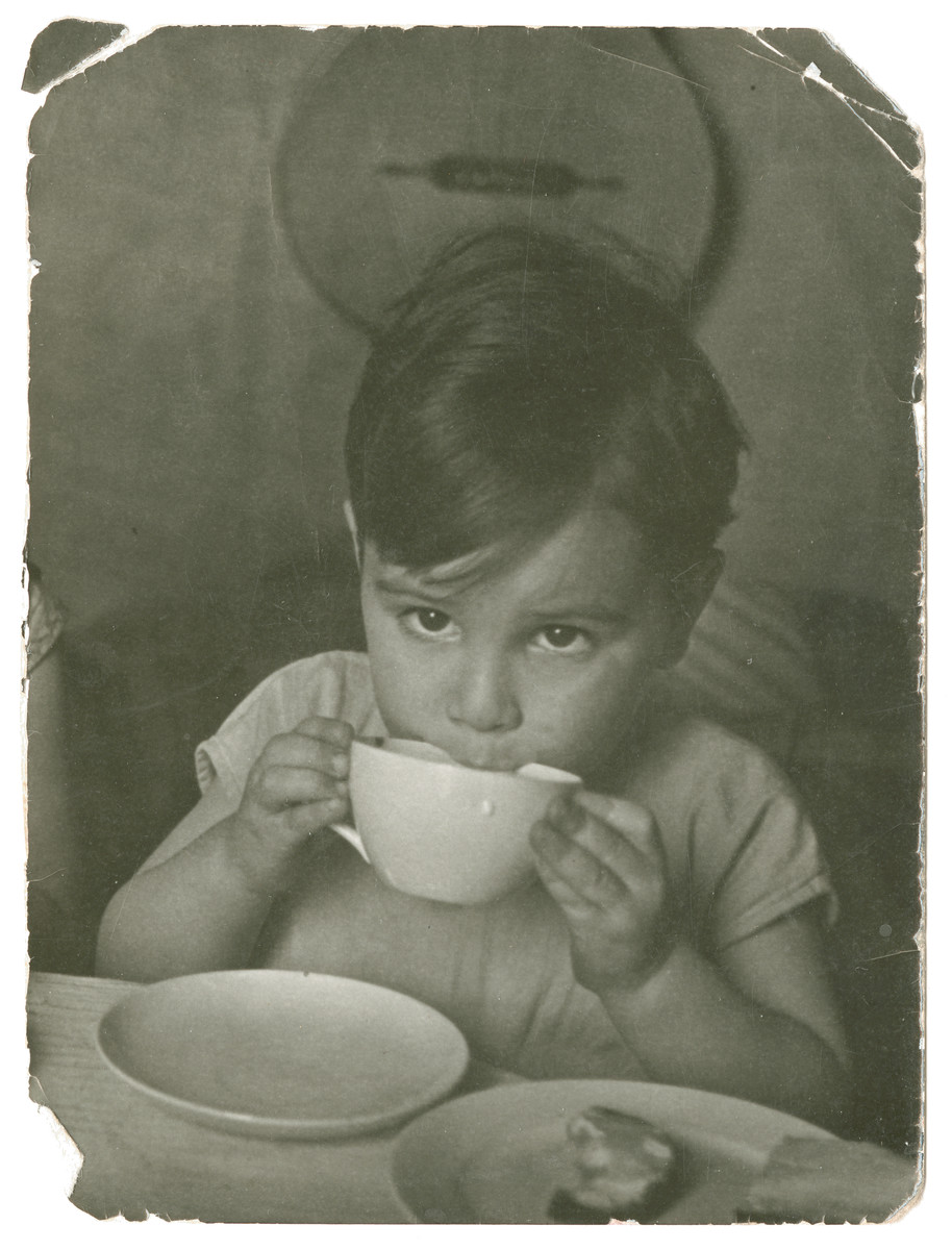 A young boy drinks from a large cup in Chateau-le-Masgelier.